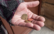 closeup of euros coins in hand of poor woman